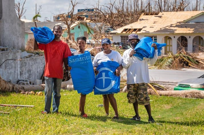 Gerald (far left) and Rosie (second from right) stand with their neighbors after receiving shelter plastic from Samaritan's Purse.