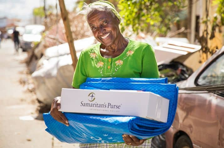 A beneficiary in Puerto Rico receives a hygiene kit and shelter plastic from Samaritan's Purse.