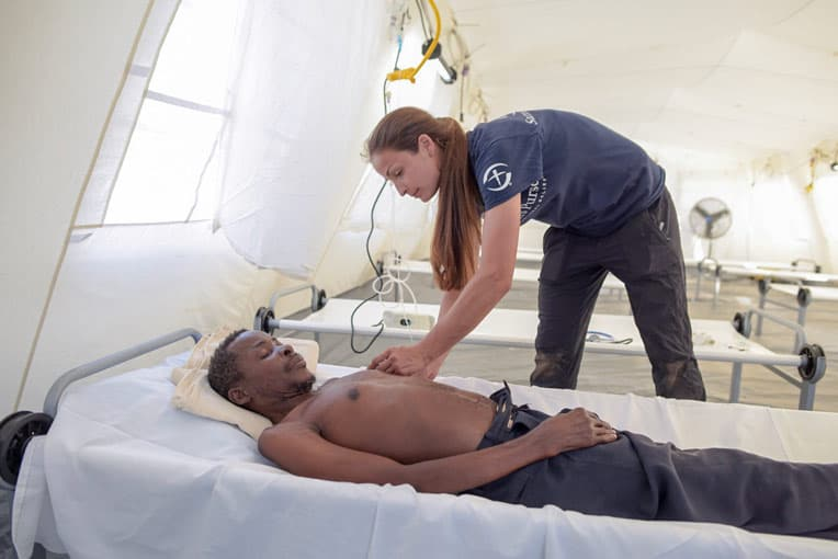 Nurse Jessica Lutz cares for Joao—our first overnight patient at the Emergency Field Hospital.