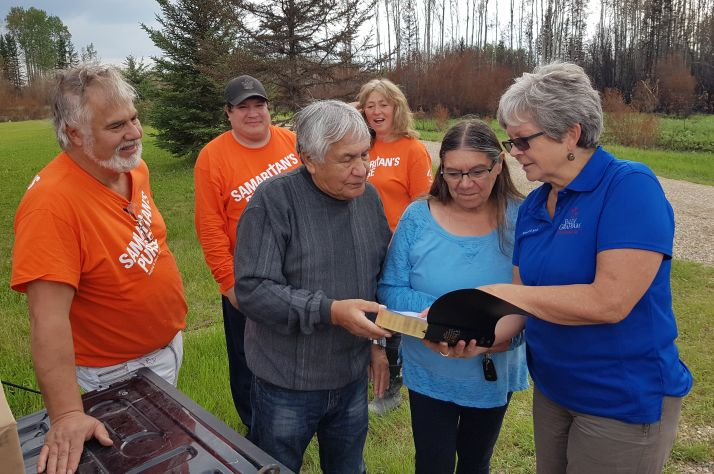 Samaritan's Purse volunteers watch while Paddle Prairie Metis Settlement residents Wilson and Jessie Gaucher receive a Bible from a Billy Graham Rapid Response Team chaplain.