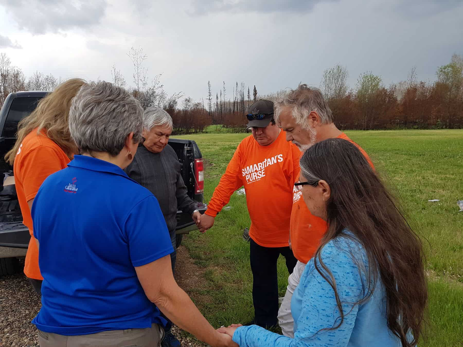 Samaritan's Purse volunteers and Billy Graham Rapid Response Team chaplains pray with homeowners.