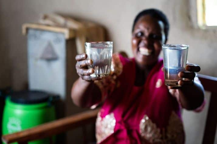 In Kenya, Alice Tum celebrates the clean water she can now drink thanks to her BioSand Filter (pictured in the background) that was supplied by Samaritan's Purse.