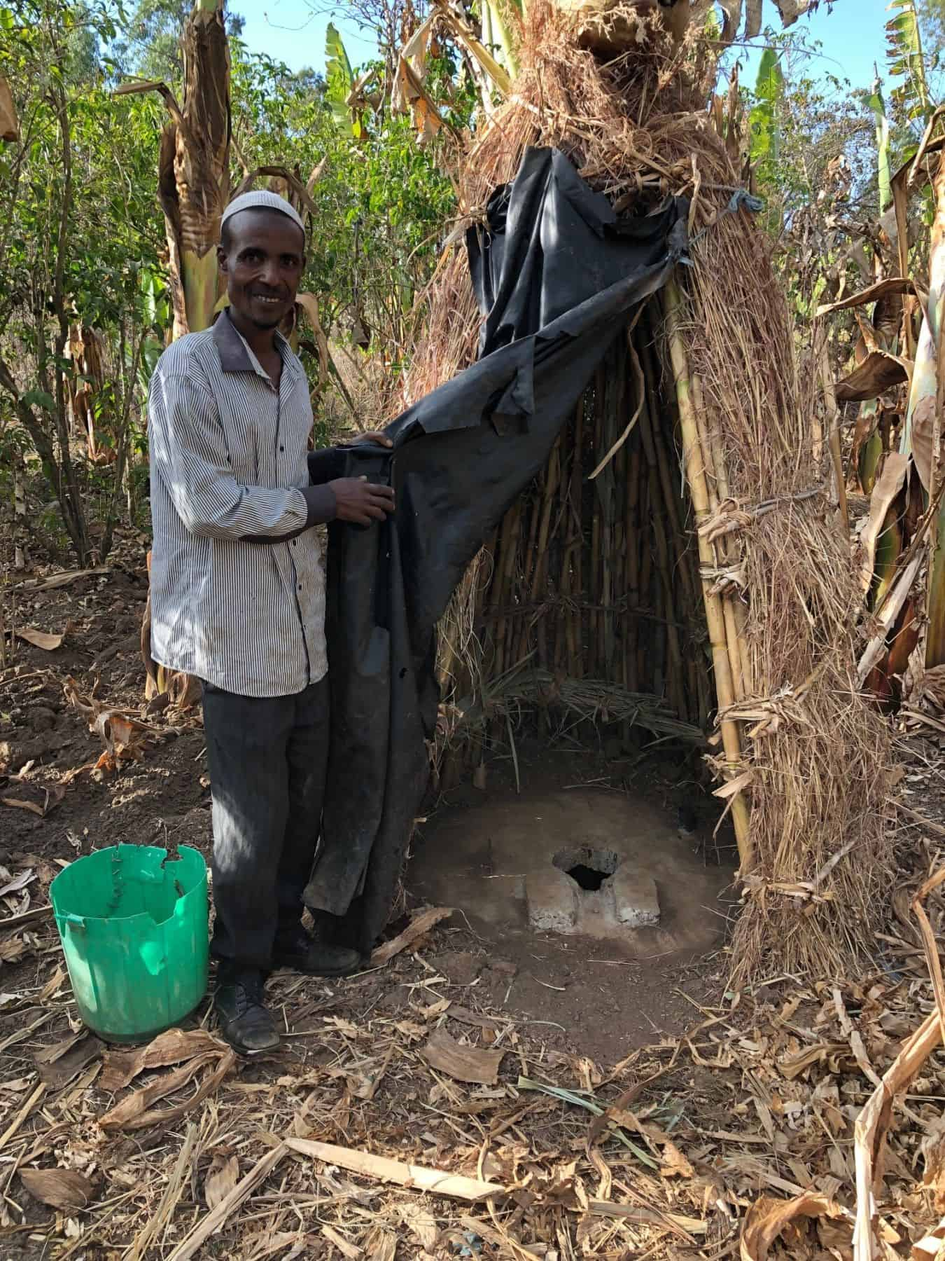 Sefa Nassir proudly showing visitors the latrine he dug and built himself, after our health and hygiene training taught him the importance of using latrines.