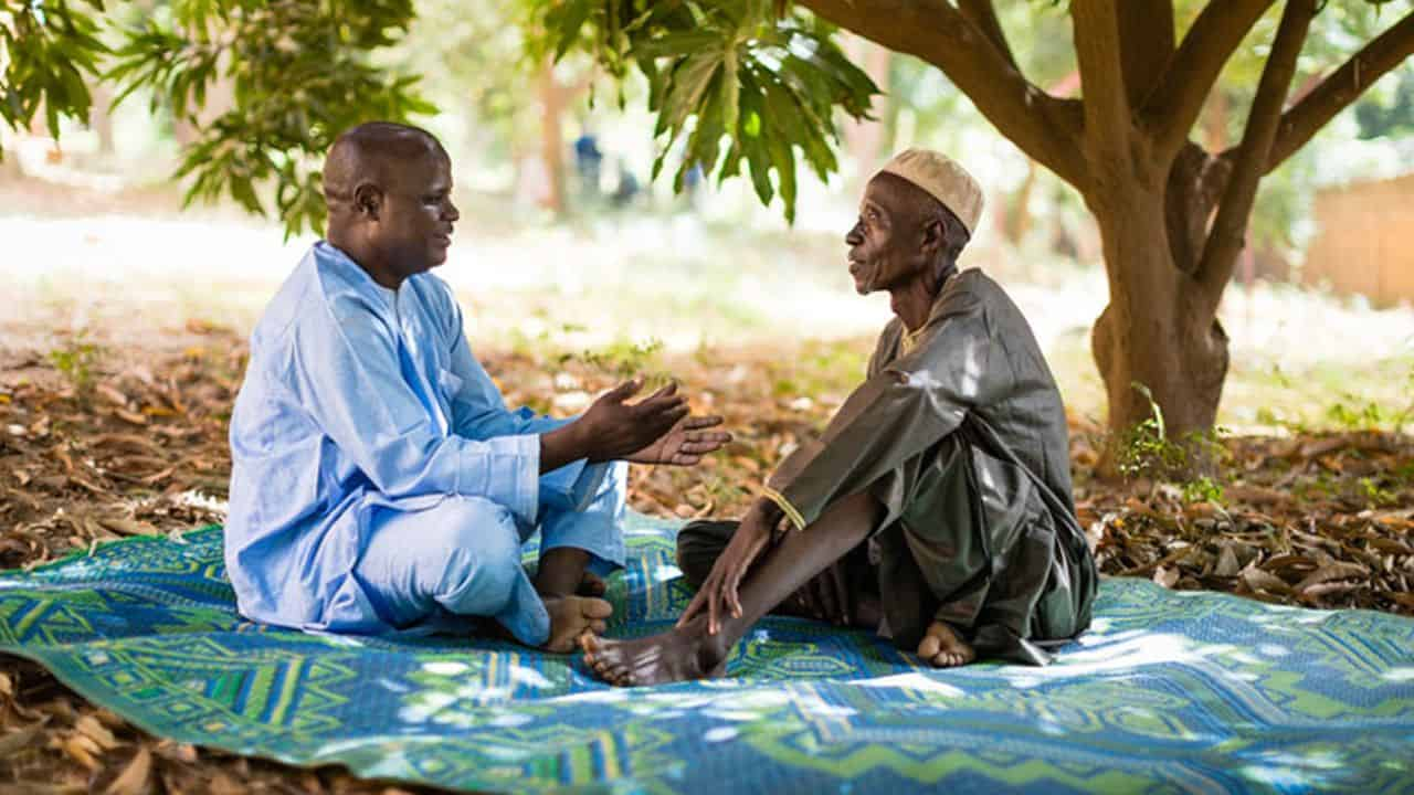 Abdou Issa and Ibrahim Sani discuss scripture under a mango tree. Ibrahim was led to salvation in Jesus Christ after Abdou preached the Gospel in his village.