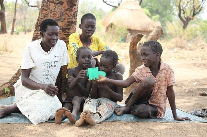 South Sudanese refugee Mary Joro enjoys some cool, clean water from a newly drilled Samaritan's Purse well with four of the eight children who are currently under her care.