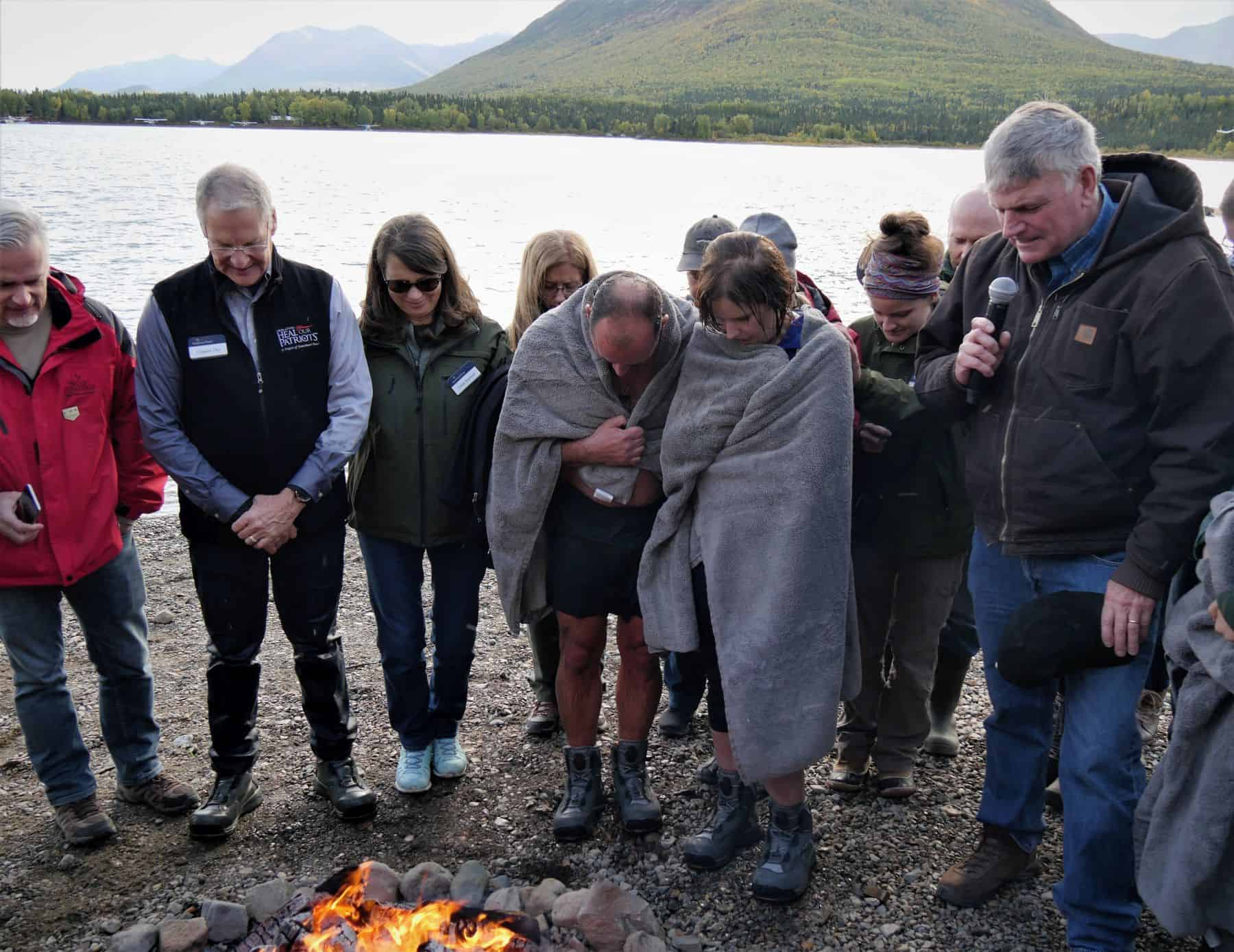 After six people were baptized in the chilly waters of Lake Clark, Samaritan's Purse international president Franklin Graham prayed with them to encourage them in their new faith.