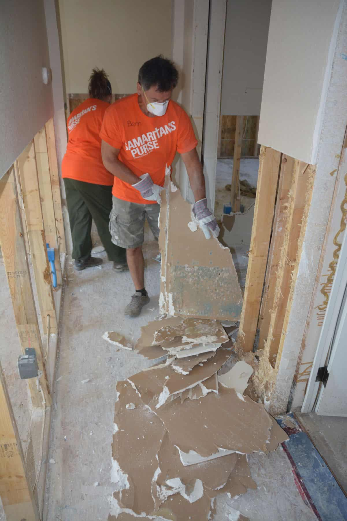 A Samaritan's Purse volunteer helps strip away moldy drywall in Grand Forks, B.C.
