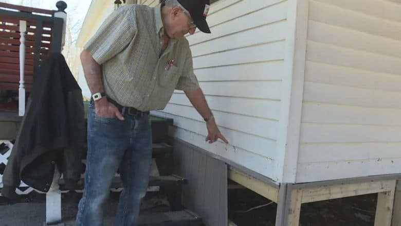 Earl Leblanc points to where the water reached on his mobile home in Maugerville. (Shane Fowler/CBC)