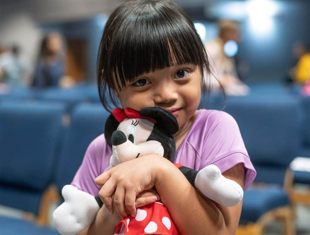 A girl hugs a favorite toy she received in her shoebox.