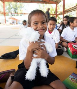 A student at Peleliu Elementary School in Palau hugs a favorite shoebox gift. The festive outreach event was the first ever in Palau.
