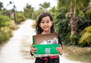 A shoebox recipient on the Pacific island of Saipan proudly shows off the gifts she received.