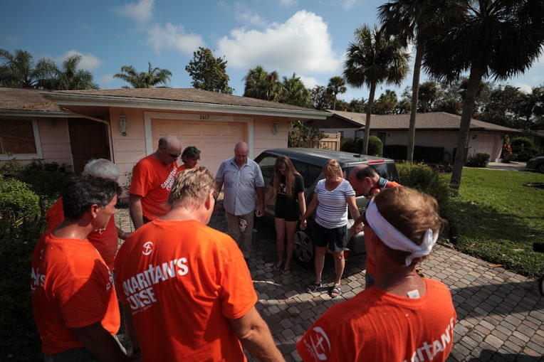 Our volunteers pray with a family in Naples, Florida, after helping remove fallen trees from their yard.