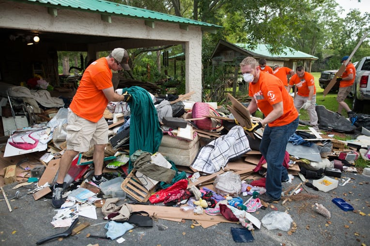 Volunteers in Santa Fe sort through a homeowner's damaged belongings.