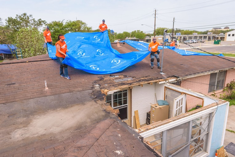Volunteers in Victoria, Texas, are tarping roofs that were damaged or destroyed during Hurricane Harvey.